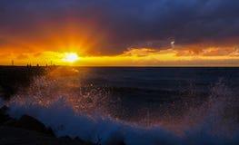 Solnedgång vid vågorna av havet Arkivfoto
