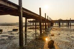 Solnedgångbakgrund och träbro arkivbild