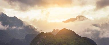 Solnedgångberg med dimman på Chiangrai Arkivfoto
