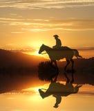 Solnedgångcowboy vid en sjö i bergen Royaltyfri Fotografi