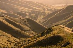 Solnedgången över dalen vissnar in kullar Arkivfoto