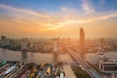 Solnedgången över den Bangkok staden som var i stadens centrum med floden, buktade flyg- sikt Arkivfoton