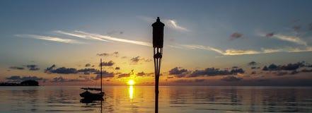 Solnedgången över den Stillahavs- västkustenhavstranden med segelbåten och facklan tänder Arkivbild
