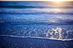 Solnedgången över ett lugna hav med att svepa vinkar royaltyfri foto