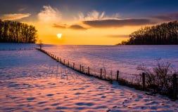 Solnedgången över ett staket i en snö täckte lantgårdfältet i lantliga Carrol Royaltyfri Foto