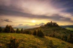 Solnedgången över fördärvar av den Spis slotten i Slovakien Arkivfoto