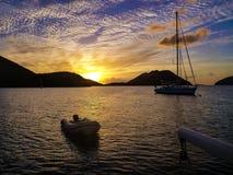 Solnedgången över havet och seglar Arkivbild