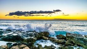 Solnedgången över horisonten med några fördunklar och de steniga kusterna av västkusten av Oahu Royaltyfria Bilder