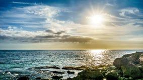 Solnedgången över horisonten med några fördunklar på den steniga kustparadislilla viken Royaltyfria Bilder