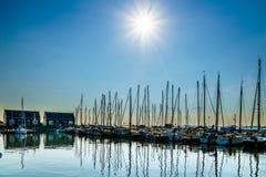 Solnedgången över seglar fartyg som förtöjas i den lilla hamnen av det historiska fiskeläget av Marken Royaltyfri Bild