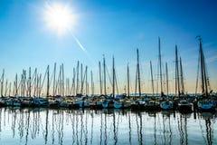 Solnedgången över seglar fartyg som förtöjas i den lilla hamnen av det historiska fiskeläget av Marken Arkivfoto
