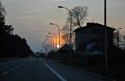 Solnedgången över vägen med gatalampor Arkivfoto