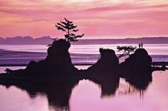 Solnedgången av havstranden med vaggar bildande och rosa färger och purpurfärgade signaler av ljus Fotografering för Bildbyråer