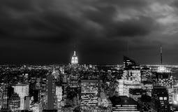 Solnedgången av vaggar uppifrån - Empire State Building tände i mitten som lämnades av ramen - i svartvitt royaltyfria bilder