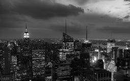 Solnedgången av vaggar uppifrån - Empire State Building tände till vänstersidan av ramen royaltyfri bild