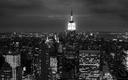 Solnedgången av vaggar uppifrån - Empire State Building tände upp i mitten av ramen - i svartvitt royaltyfria foton