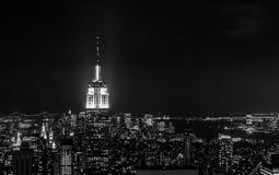 Solnedgången av vaggar uppifrån - Empire State Buildinghöjdpunkten som tänds ljust till vänstersidan av ramen - i svartvitt royaltyfri fotografi