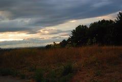 Solnedgången avslutar en tidig nedgångdag över ettfärgat fält Royaltyfri Fotografi