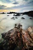 Stenig strand på solnedgången Royaltyfria Foton
