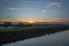 Solnedgången bland betar Arkivfoto
