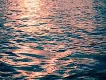 Solnedgången exponerar blåa vågor i stuga sjön arkivbild