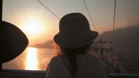 Solnedgången för elevatorn för kabel för konturflickan flyttar sig tycker om den turist-, ner, sikten av havet och bergen stock video