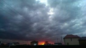 Solnedgången fördunklar på by Arkivbilder