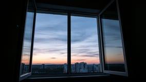 Solnedgången fördunklar till och med ett fönster med en reflexion i fönstersidohängda fönstret arkivfoto