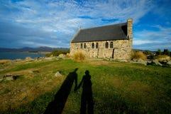 Solnedgången gjuter vår (mig & min fru) hand i hand skugga till en gammal kyrka Arkivfoton