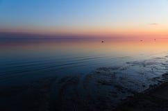 Solnedgången i rött, blått, rosa, guling färgar på havet Arkivfoto