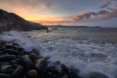 Solnedgången i vaggar stranden royaltyfri foto