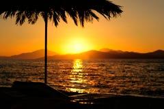 Solnedgången med berg, havet och gömma i handflatan Royaltyfria Bilder