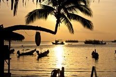 Solnedgången med gömma i handflatan och fartyg på den tropiska stranden. Ko Tao ö, Arkivfoton