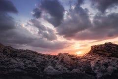 Solnedgången med moln och vaggar Fotografering för Bildbyråer
