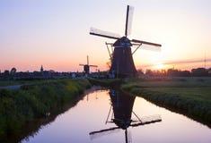 Solnedgången med traditionella holländska väderkvarnar reflekterade i den lugna waen Royaltyfri Foto