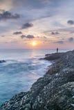 Solnedgången med vågor plaskar på kust, och vaggar den främre Stillahavs- ostron för blurr på andamanhavet Arkivfoto