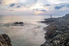 Solnedgången med vågor plaskar på kust, och vaggar den främre Stillahavs- ostron för blurr på andamanhavet Arkivbilder