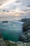 Solnedgången med vågor plaskar på kust, och vaggar den främre Stillahavs- ostron för blurr på havet för surinstrandandamanen Arkivfoton