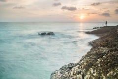 Solnedgången med vågor plaskar på kust, och vaggar den främre Stillahavs- ostron för blurr på surinstranden Royaltyfria Foton
