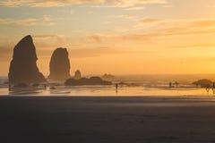 Solnedgången med vaggar buntar på kusten Arkivfoton