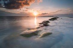 Solnedgången ovanför en leanding linje vaggar Arkivbild