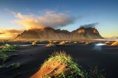 Solnedgången ovanför Vestrahorn och dess svarta sand sätter på land i Island royaltyfri foto