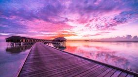 Solnedgången på den Maldiverna ön, lyxiga vattenvillor tillgriper och träpir Härlig himmel och moln och lyxig strandbakgrund royaltyfri foto
