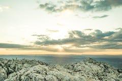Solnedgången på ett berg med vaggar i förgrunden royaltyfri bild