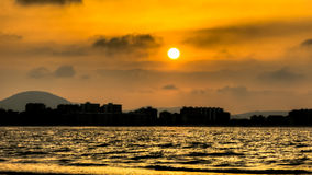 Solnedgången på staden och havet Royaltyfria Bilder