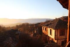 Solnedgången på stenen belade med tegel tak av den Leshten byn Royaltyfri Fotografi