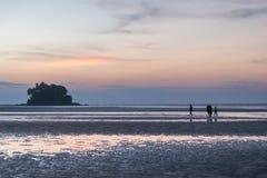 Solnedgången på stranden med folk går på stranden Fotografering för Bildbyråer