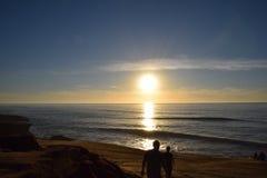 Solnedgången promenerar stranden med vågor arkivfoton