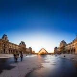 Solnedgången skiner till och med den glass pyramiden av Louvremuseet Royaltyfri Bild