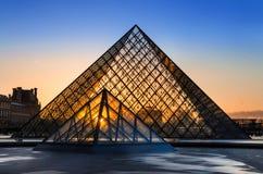 Solnedgången skiner till och med den glass pyramiden av Louvremuseet Royaltyfri Foto